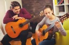 Guitar tutor giving lesson | adriaticfoto/Shutterstock.com