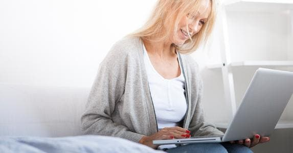 Woman smiling using her webcam © iStock