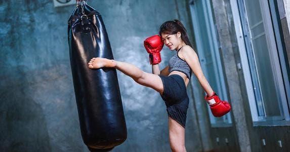 Woman kickboxing in gym | Woraphon Nusen/Shutterstock.com