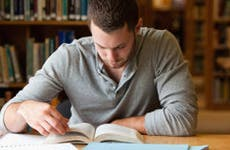 Male student researching with a book © wavebreakmedia/Shutterstock.com
