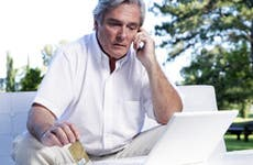 Older man sitting outside, on phone holding Amex card © iceteastock - Fotolia.com