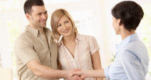 Happy young couple man shaking hands with a realtor © StockLite/Shutterstock.com