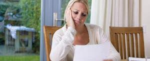 Woman looking sadly at paper