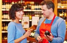 Salesman in supermarket offering red wine to customer © Robert Kneschke/Shutterstock.com