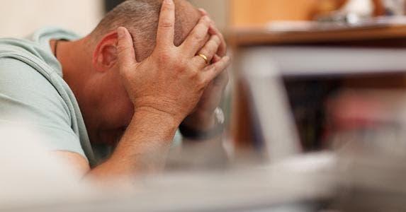 Man with head in hands © d13/Shutterstock.com