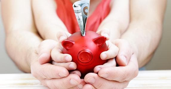 Father and child holding red piggy bank © iStock