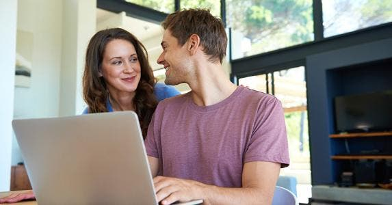 Happy couple browsing laptop computer © iStock