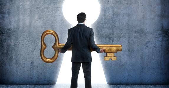 Man holding large key at keyhole doorway © iStock