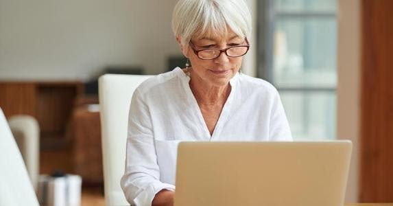 Senior woman using her laptop in a bedroom © iStock