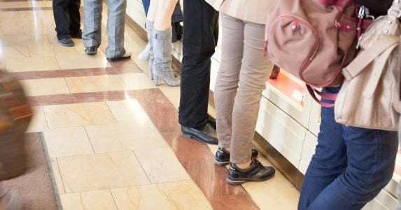 Many people standing at bank counter © iStock
