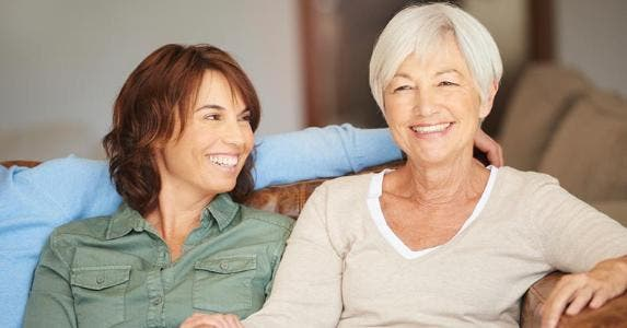 Mother and daughter sitting together on the couch © iStock