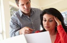 Couple looking over binder of papers © iStock