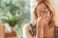 Stressed woman pinching bridge of nose | Tetra Images/Getty Images