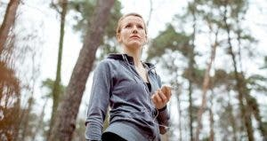 Woman holding mp3 player, running in the woods | Luis Alvarez/DigitalVision/Getty Images