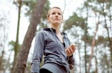 Woman holding mp3 player, running in the woods   Luis Alvarez/DigitalVision/Getty Images
