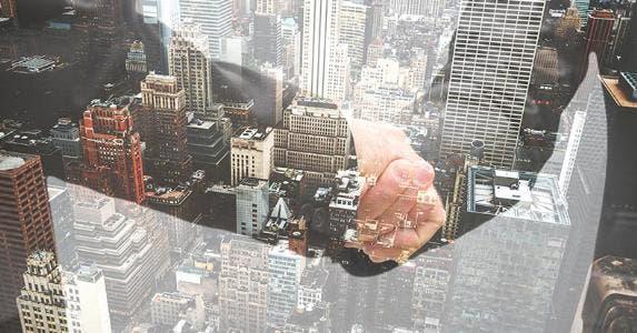 Businessmen shaking hands, window reflecting city below   franckreporter/Getty Images