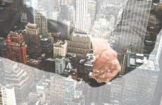 Businessmen shaking hands, window reflecting city below | franckreporter/Getty Images