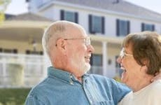 Laughing senior couple standing in front of house © Andy Dean Photography/Shutterstock.com