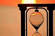 Hourglass and sunset background   iStock.com/Leslie Achtymichuk