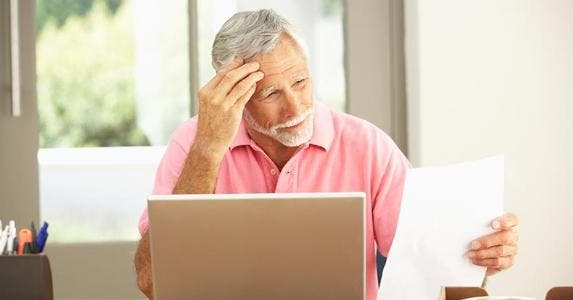 Worried senior man in pink shirt reading paper, laptop on table | iStock.com/monkeybusinessimages