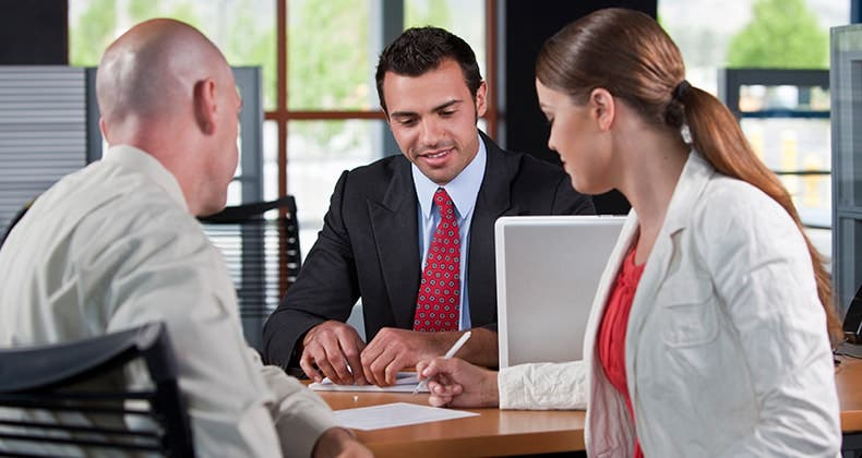 Couple signing a contract in agent's office © iStock
