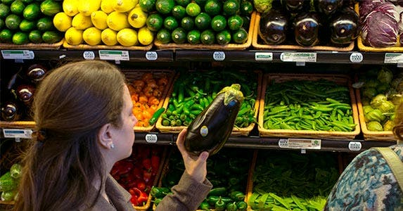 Woman looking at an eggplant at the grocery store