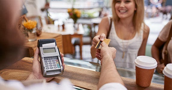 Woman handing credit card to cashier