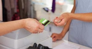 Woman handing credit card to pay in store © racorn/Shutterstock.com