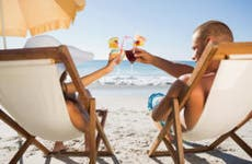 Couple on beach with drinks © wavebreakmedia/Shutterstock.com