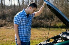 Man looking under the hood of his car © iStock