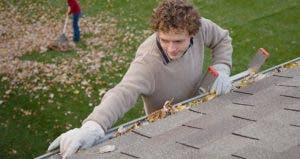 Man removing dead leaves from rain gutters | DreamPictures/VStock/Getty Images