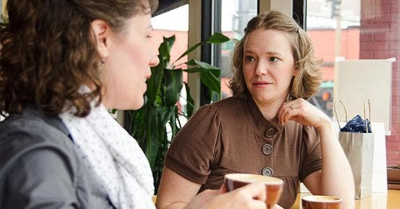 Two women chatting inside coffee shop © iStock