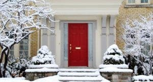 Front door of a house covered in snow © Pete Spiro/Shutterstock.com