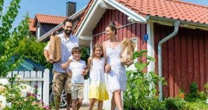 Young familiy holding bag of groceries outside home © Kzenon/Shutterstock.com