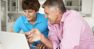 Father and teenage son using laptop in kitchen © Monkey Business Images/Shutterstock.com
