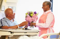 Mature female volunteer worker tidying male patient's hospital room © Monkey Business Images/Shutterstock.com