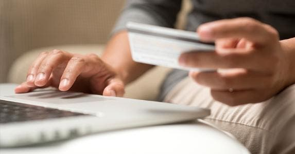 Man holding credit card while using laptop © iStock