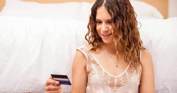 Woman using credit card online © iStock