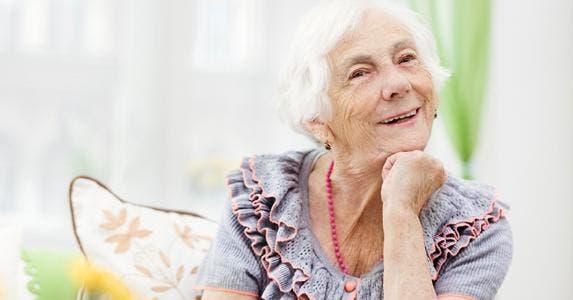 Senior woman laughing in sunroom © iStock