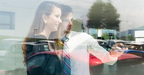 Salesman showing car from window © iStock