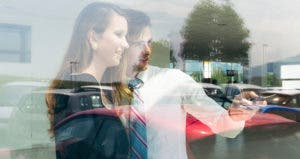 Salesman showing car from window © iStock