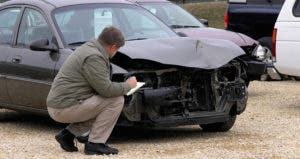 Insurance claims adjuster evaluating wrecked car