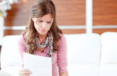 Woman wearing pink top and scarf reading paperwork in sofa © iStock