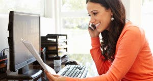 Smiling woman talking on the phone while reading paperwork