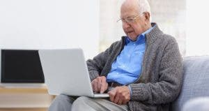 Senior man sitting on couch with laptop