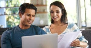 Couple happily budgeting together © iStock