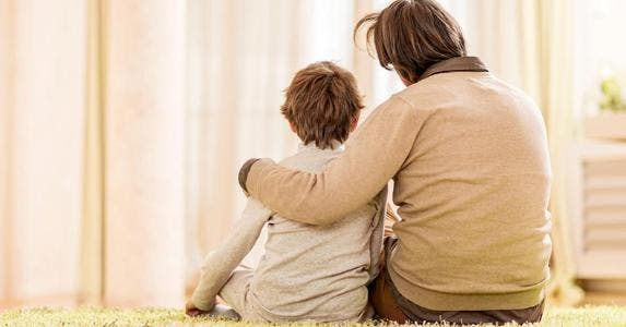 Father and son sitting on rug in beige room   iStock.com/skynesher