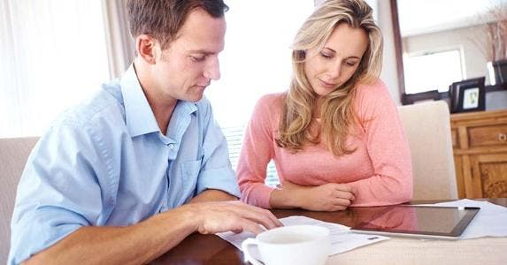 Couple going over papework and tablet computer on kitchen table | iStock.com/shapecharge