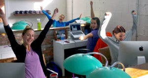 Young workers cheering from their desks | Photo courtesy of Kyle Taylor
