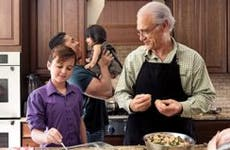 Family cooks a meal together | Lise Gagne/Getty Images